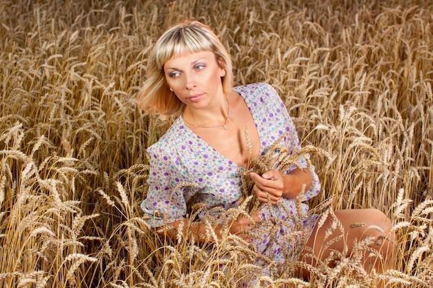 Belle femme assise sur un champ de blé
