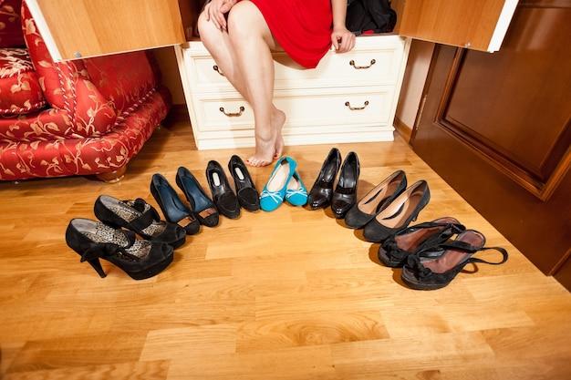 Belle femme assise dans une armoire parmi des chaussures à talons hauts et des ballerines