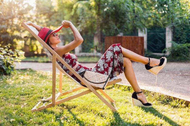 Belle femme assise dans une chaise longue en tenue tropicale. dame dans la tendance de la mode estivale de style rue. portant un sac à main en paille, un chapeau rouge, des lunettes de soleil. fille élégante souriant de bonne humeur en vacances.