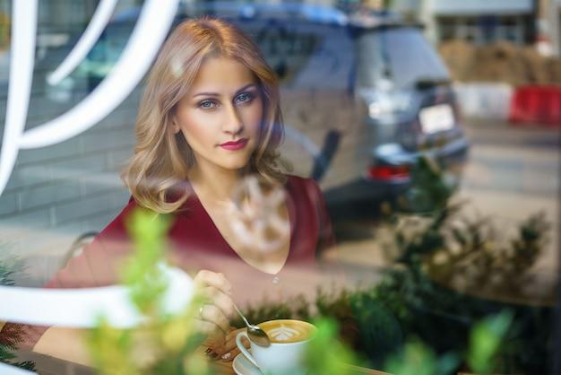 Belle femme assise à la fenêtre dans un café en buvant du café.