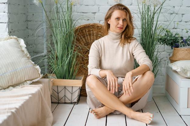 Belle femme assise à la maison sur un plancher en bois