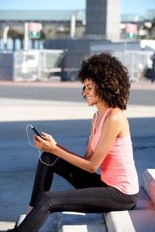 Belle femme assise sur les marches en écoutant de la musique sur téléphone portable