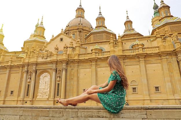 Belle femme assise sur le mur avec la basilique de notre-dame du pilier à saragosse, espagne