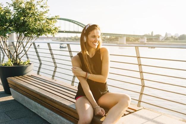 Belle femme assise à proximité de la rivière en écoutant de la musique