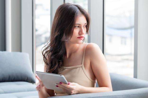 Belle femme assise et shopping en ligne avec tablette dans le salon.