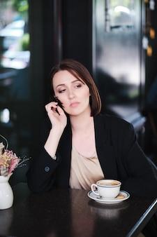 Belle femme assise à table dans un café