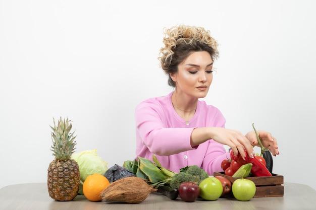 Belle femme assise à table avec divers fruits et légumes frais.