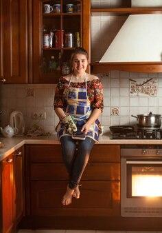 Belle femme assise sur une table pendant la cuisson du dîner au four