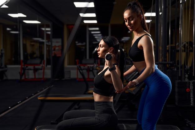 Belle femme athlète exerçant avec des haltères dans un club de remise en forme