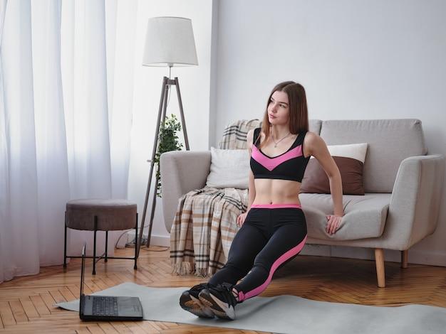 Belle femme athlétique faisant de la gymnastique à la maison