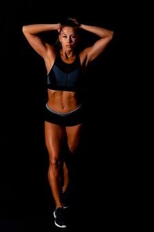 Belle femme athlétique montrant des muscles sur fond sombre corps de femme bronzée mince sur mur noir