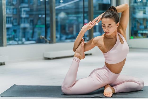 Belle femme athlétique s'entraînant dans une salle de sport, faisant des exercices d'étirement avant l'entraînement