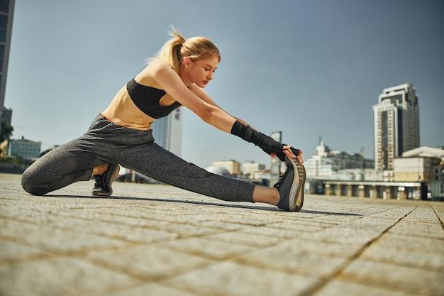 Belle femme athlétique en tenue de sport étire les jambes et regarde sa jambe dans la rue