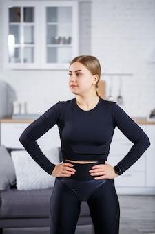 Une belle femme athlétique vêtue d'un haut noir et de leggings montre une silhouette élancée. motivation à faire du sport. mode de vie sain.