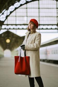 Belle femme attend le train sur la gare. fille voyage léger. femme d'âge moyen