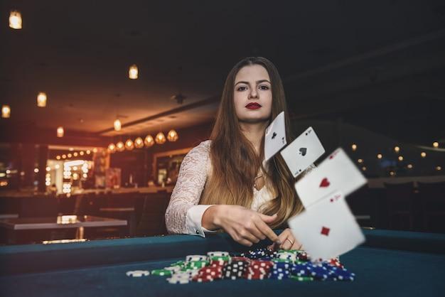 Belle femme au casino jetant des cartes à jouer
