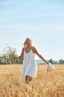 Belle femme au chapeau et avec un bouquet de fleurs sur le champ de blé en journée d'été ensoleillée