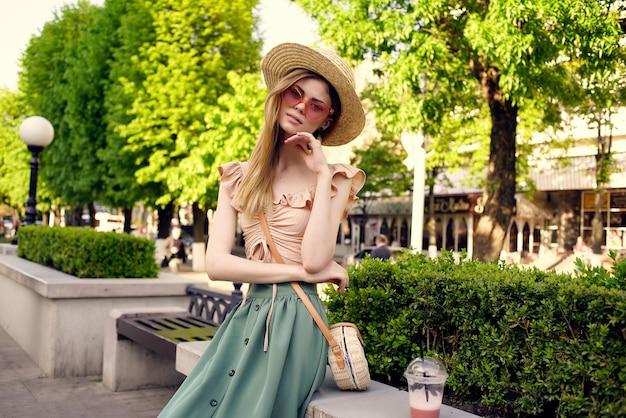 Belle femme au chapeau dans le parc boire de l'air frais au repos