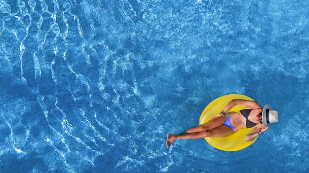 Belle femme au chapeau dans la piscine vue aérienne d'en haut, la jeune fille se détend et s'amuse sur l'anneau gonflable