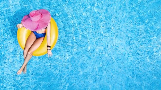 Belle femme au chapeau dans la piscine vue de dessus aérienne d'en haut, jeune fille en bikini se détend et nage sur un anneau gonflable et s'amuse dans l'eau, station balnéaire tropicale