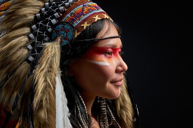 Belle femme au chapeau indien avec des plumes