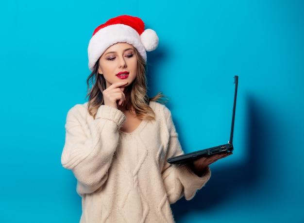 Belle femme au chapeau de noël avec ordinateur portable sur le mur bleu