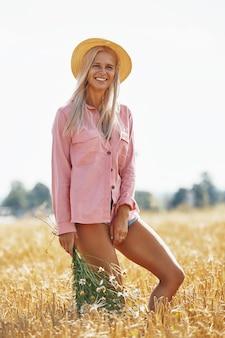 Belle femme au chapeau et avec un panier de marguerites des champs en journée d'été ensoleillée.