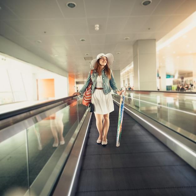Belle femme au chapeau avec sac à main debout sur la ligne d'escalator à l'aéroport