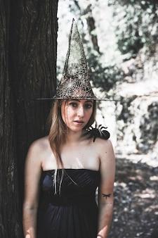 Belle femme au chapeau de sorcière debout près d'un arbre et regardant la caméra