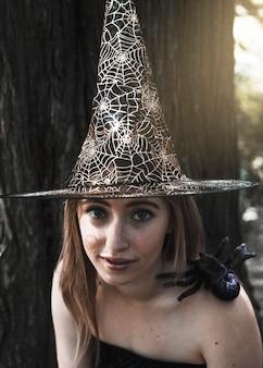 Belle femme au chapeau de sorcière regardant la caméra avec une araignée décorative assis sur l'épaule