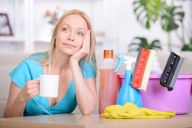 Belle femme au foyer, buvant du thé pendant le nettoyage à la maison