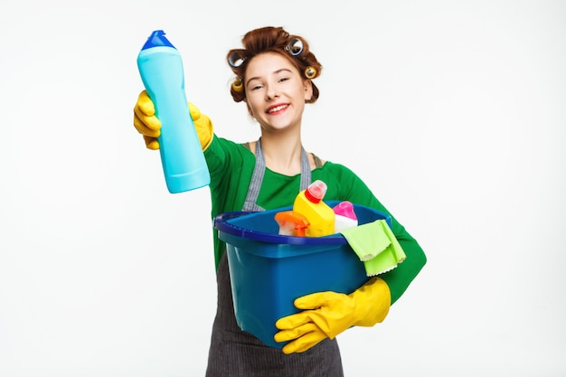 Belle femme au foyer détient des outils de nettoyage et montre une bouteille