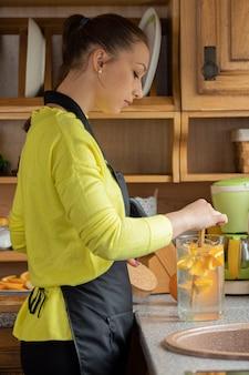 Belle femme au foyer mélange de la limonade de fruits fraîchement préparée avec des oranges
