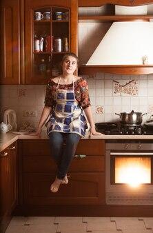 Belle femme au foyer s'asseyant sur la table près du four fonctionnant
