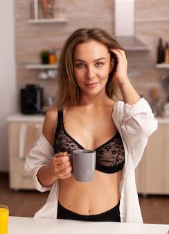 Belle femme au foyer souriante pendant le petit déjeuner dans la cuisine de la maison en lingerie noire sexy. jeune femme séduisante avec des tatouages en sous-vêtements séduisants tenant une tasse de thé se relaxant dans la cuisine en souriant.