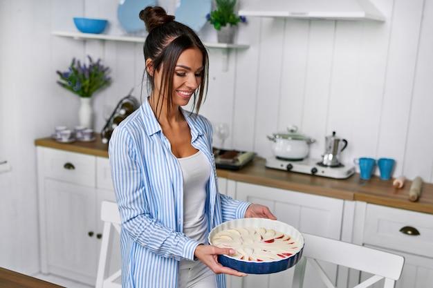 Une belle femme au foyer va faire une tarte aux pommes