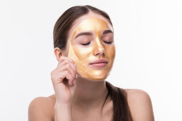 Belle femme au visage tactile cosmétique peau dorée isolé sur mur blanc. soins et soins de beauté