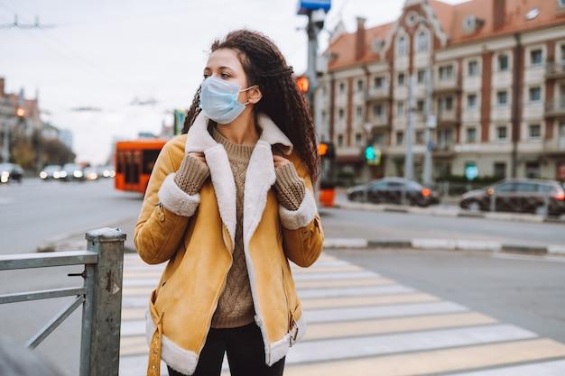 Belle femme aux cheveux afro portant un masque médical de protection se tient dans la rue de la ville.