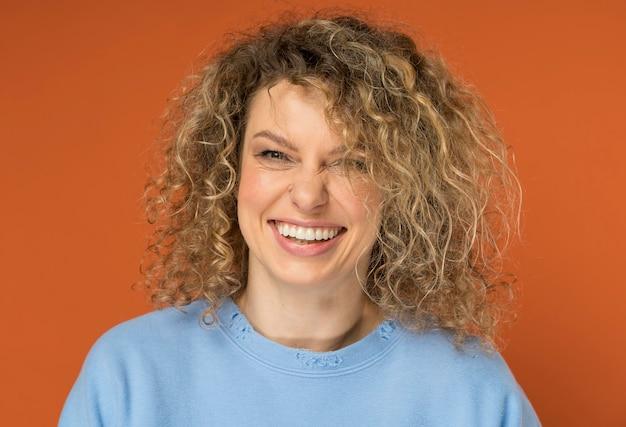 Belle femme aux cheveux blonds bouclés souriant