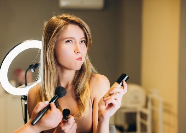 Belle femme aux cheveux blonds tient des cosmétiques dans ses mains. une cliente maquillée n'est pas contente du résultat.