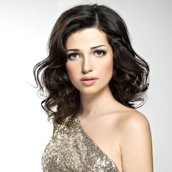 Belle femme aux cheveux bouclés broun posant