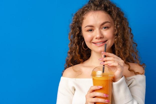 Belle femme aux cheveux bouclés buvant du jus d'orange sur fond bleu