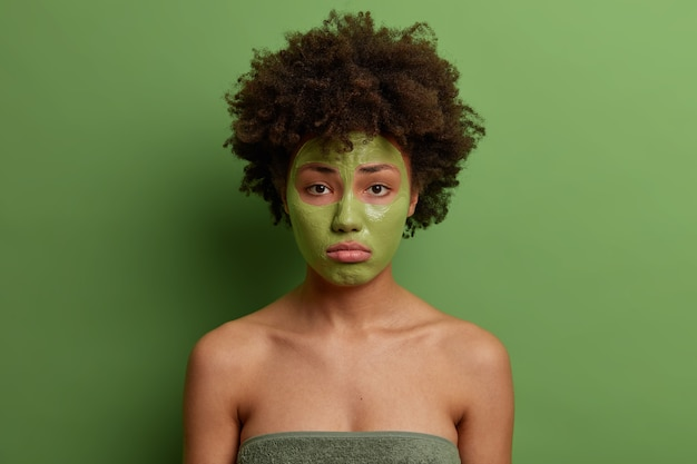 Belle femme aux cheveux bouclés moelleux applique un masque pour réduire les ridules, veut rester jeune, utilise un produit anti-âge, a une expression malheureuse, isolée sur un mur vert. concept de soins de la peau