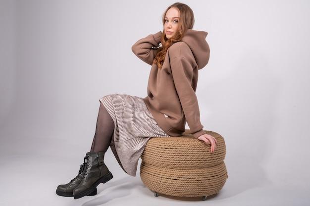Belle femme aux cheveux bouclés en sweat à capuche taupe et une jupe longue assise sur un pouf en osier
