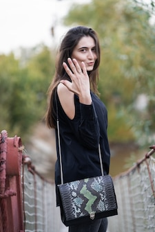 Belle femme aux cheveux brune dans des vêtements sombres et des lunettes de soleil. photographie de rue de mode. le mannequin est debout sur un pont suspendu et montre un anneau sur la nature. elle a dit oui