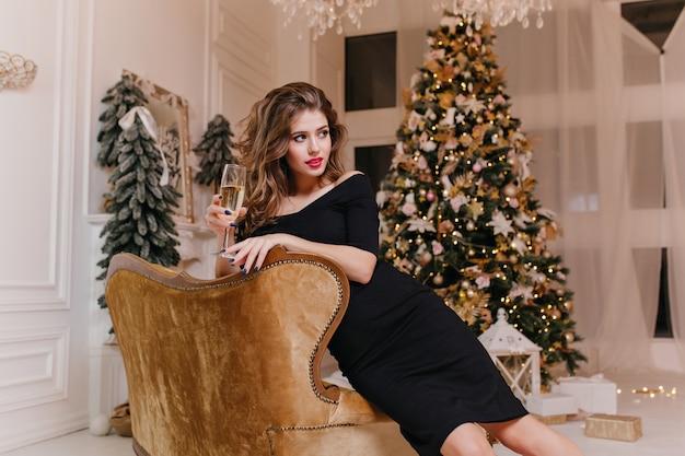 Belle femme aux cheveux bruns avec une excellente manucure et une robe moulante noire, posant dans une salle blanche avec des décorations de noël et un arbre de noël