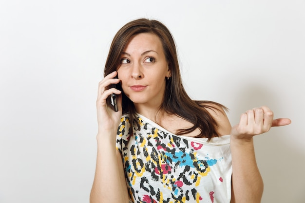 La belle femme aux cheveux bruns sérieuse perplexe parlant au téléphone portable sur fond blanc. notion d'émotions.