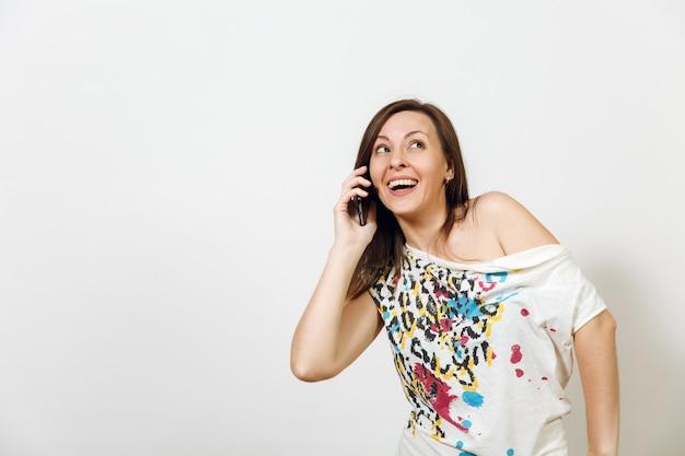 La belle femme aux cheveux bruns souriante et heureuse parlant au téléphone portable sur fond blanc. notion d'émotions.