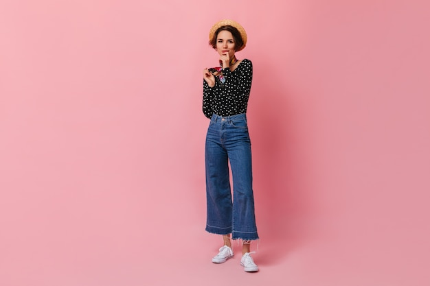 Belle femme aux cheveux courts en chapeau de paille debout sur un mur rose
