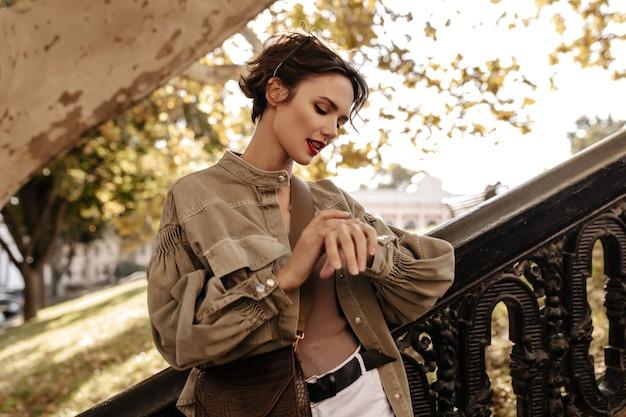 Belle femme aux cheveux courts en veste olive regarde la montre à l'extérieur. femme brune avec sac à main avec des lèvres brillantes pose à l'extérieur.